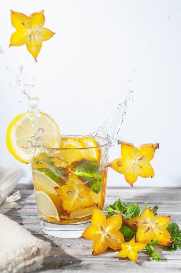 Stjärnafrukt faller med en färgstänk I en uppfriskande coctail med citruns och mintkaramellen i ett exponeringsglas Vit bakgrund  royaltyfri foto