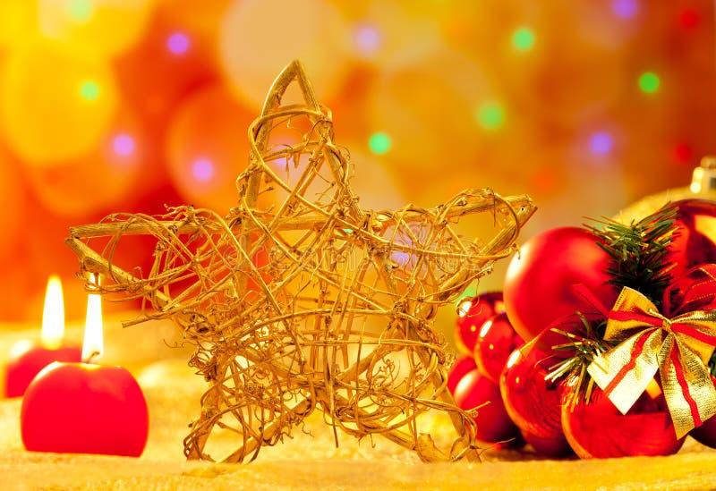 Stjärnastearinljus och baubles för jul guld- arkivfoton