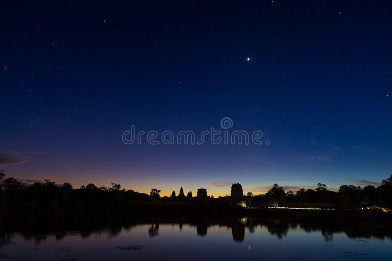 Stjärnklar himmel för Angkor Wat natt på för fasadkontur för skymning den huvudsakliga reflexionen på vattendammet Berömd tempel  royaltyfri bild