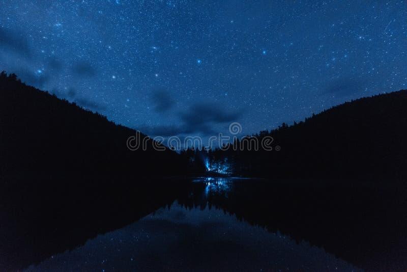 Stjärnklar himmel för natt med lotten av skinande stjärnor under den Perseid meteorregnet över den alpina sjön Synevyr i Carpathi arkivfoto