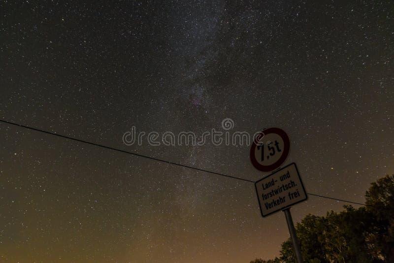 """Stjärnklar himmel med den mjölkaktiga vägen med tysk †för gatatecken """"som är fri för jordbruks- och skogsbruktrafik, Bayern, Ty arkivfoto"""