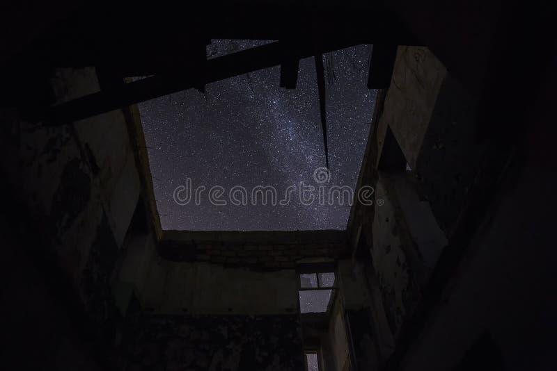 Stjärnklar himmel till och med taket i ett övergett hus arkivbild