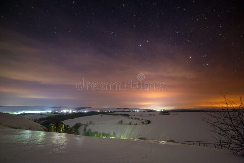 Stjärnor av natthimlen döljas av moln Snöig vinter arkivbilder