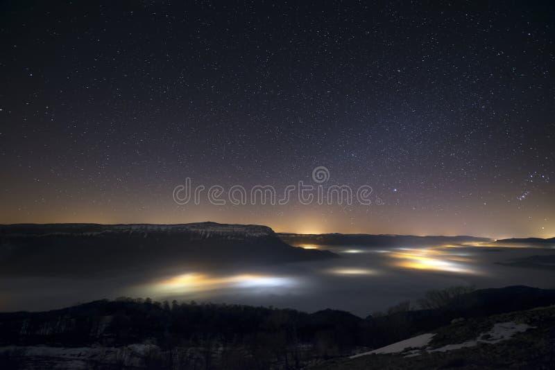 Stjärnor i en dimmig natt över dalen royaltyfri bild