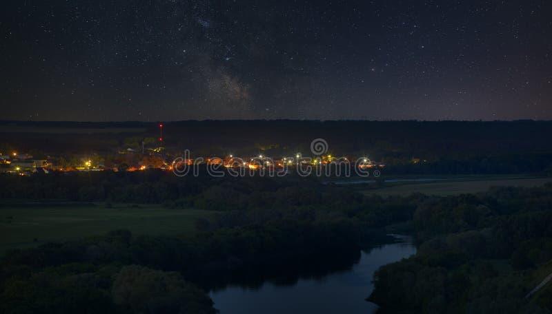 Stjärnor i natthimlen över Riveret Valley och staden arkivbilder