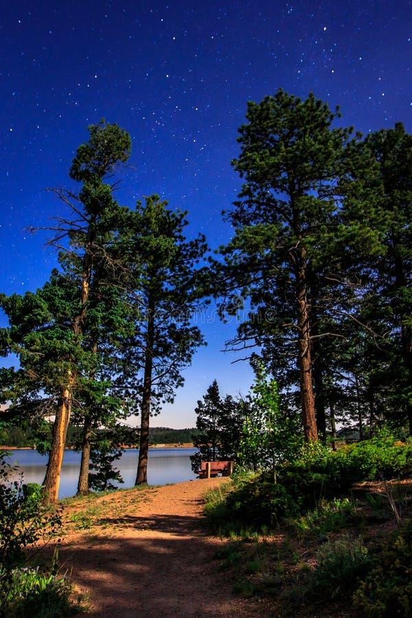 Stjärnor och sjö vid månsken på vallbehållaren arkivbild