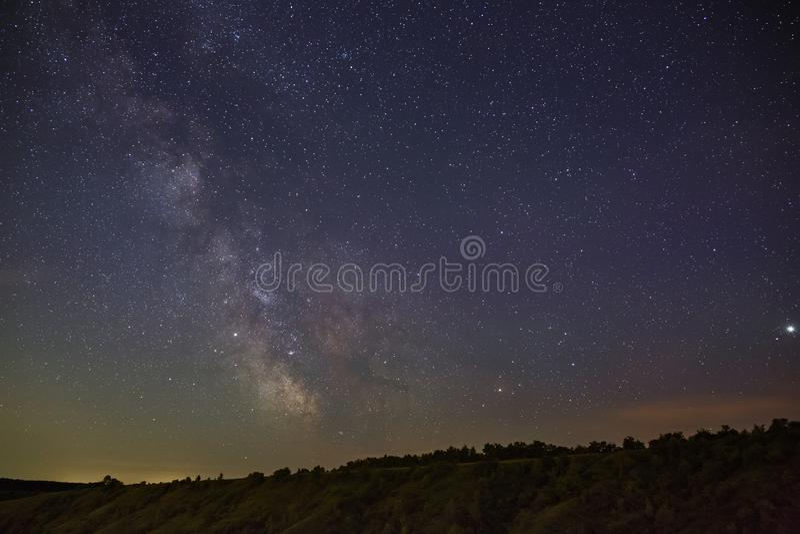 Stjärnorna av Vintergatan i natthimlen över ett bergigt landskap royaltyfria bilder