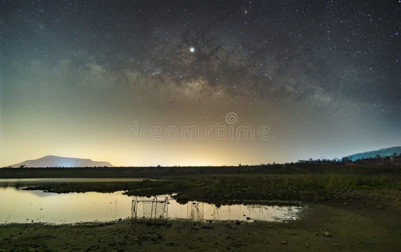 Stjärnorna i himlen reflekterar ljuset på natten Vintergatan ovanför bergen och dammet royaltyfri foto