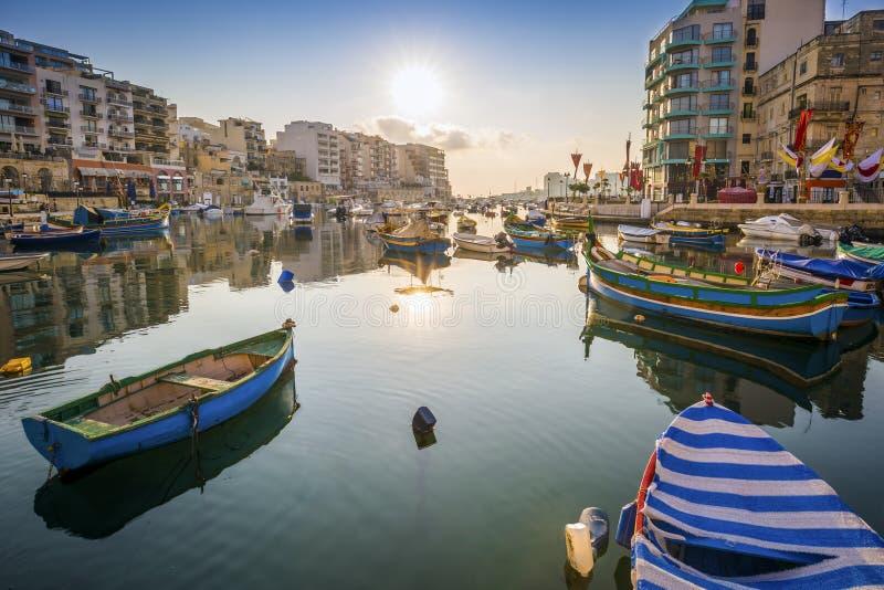 StJulian-` s, Malta - Sonnenaufgang an Spinola-Bucht mit traditionellen maltesischen Fischerbooten lizenzfreies stockfoto