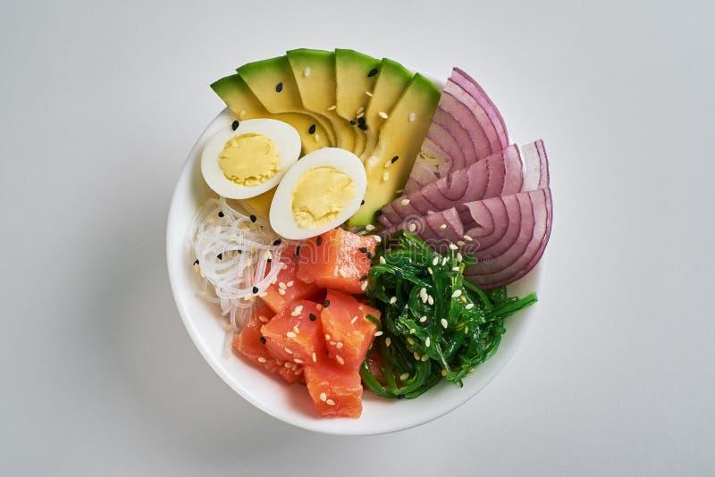 Stoßschüssel mit Lachsen, Avocado, Reis, Chuka-Salat, süße Zwiebeln, Wachteleier besprüht mit dem weißen und schwarzen indischen  lizenzfreies stockfoto