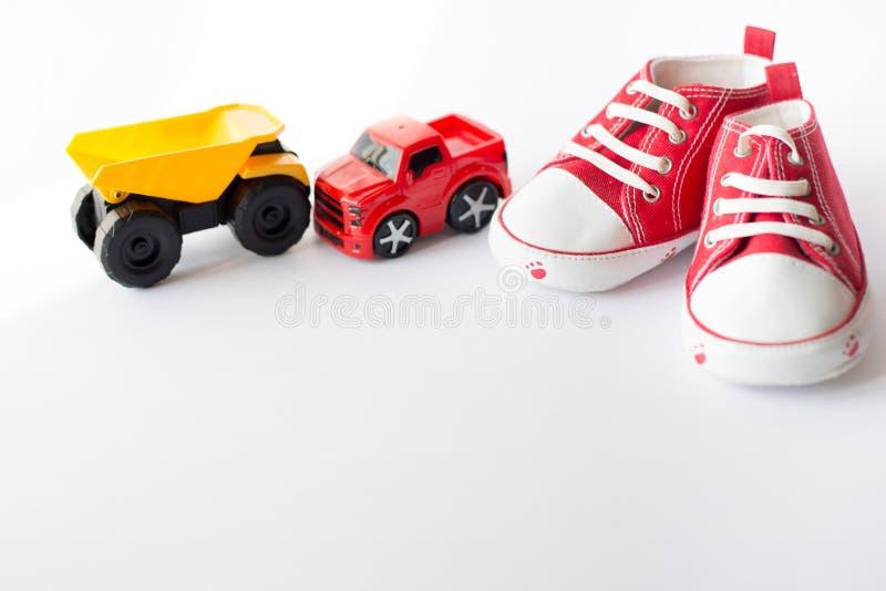 Stołowy odgórnego widoku dekoracji dzieciak bawi się samochody dla rozwija tła pojęcie Dziecko czerwieni buty obraz stock