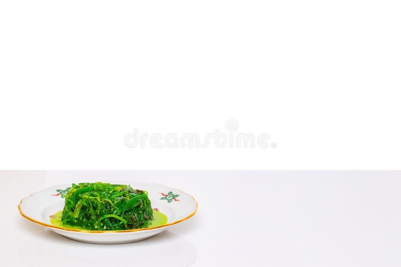 Stołowy wierzchołek na owoce morza tle Świeża chuka sałatka z sesam na talerzu na białym stole odizolowywającym na białym tle sza fotografia stock