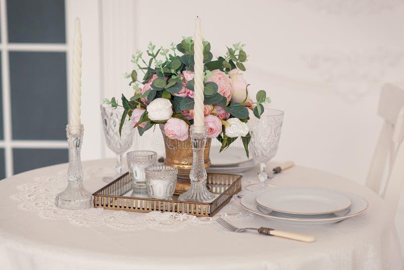 Stołowa porcja dla państwa młodzi z wystrojem, krystalicznymi szkłami i kwiatami, ślubny przygotowania róże, peonie obraz stock