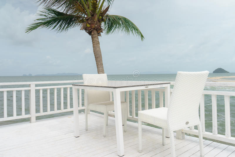 Stołowy krzesło i kokosowy drzewo na morzu zdjęcie royalty free