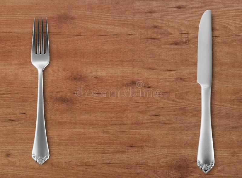 Stołowy nóż i rozwidlenie na drewnie fotografia royalty free