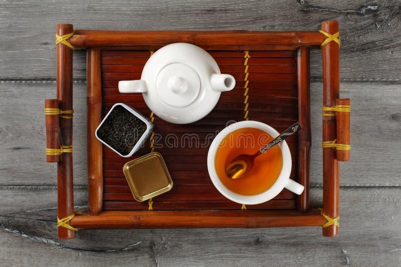Stołowy odgórny widok na białym ceramicznym teapot, filiżanka gorący czarnej herbaty dowcip zdjęcia stock