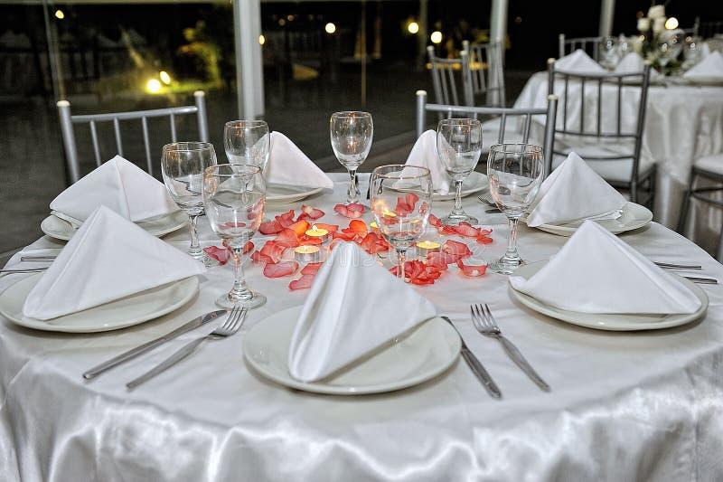 Stołowy położenie wystrój z cutlery, talerzami i szkłami dekorującymi z bukietem, peonie, różani płatki i świeczki, dalej zdjęcie royalty free