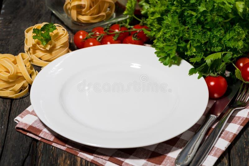 Stołowy położenie z talerzem, makaronem i warzywami na drewnianym tle bielu, fotografia royalty free