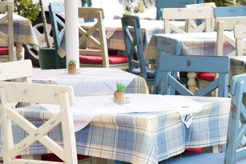 Stoły i krzesła w typowej tradycyjnej Medierranean restauracji na tarasie w kolorze bławym i białym zdjęcia stock