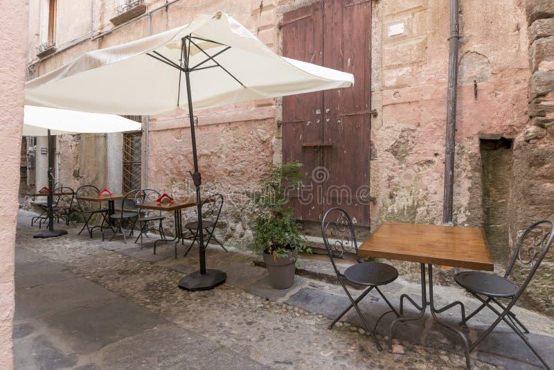 Stoły i krzesła w wąskiej alei przy Orta San Giulio, Włochy zdjęcia stock