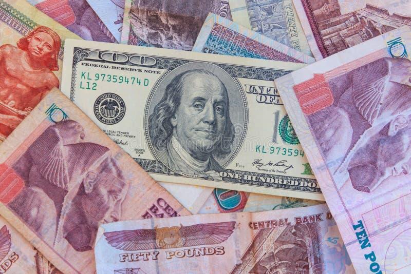 Sto dolarowych rachunków na egipskich funtów banknotów tle obrazy royalty free
