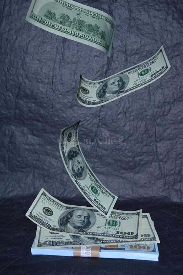 Sto dolarowych rachunków spadają na stosie pieniądze obrazy royalty free