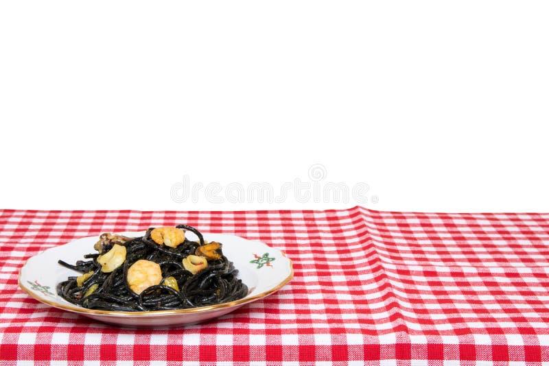 Sto?owy wierzcho?ek na owoce morza tle Zbliżenie śródziemnomorscy czarni kluski z atramentem, mussels i garnelami na czerwieni cu zdjęcie stock