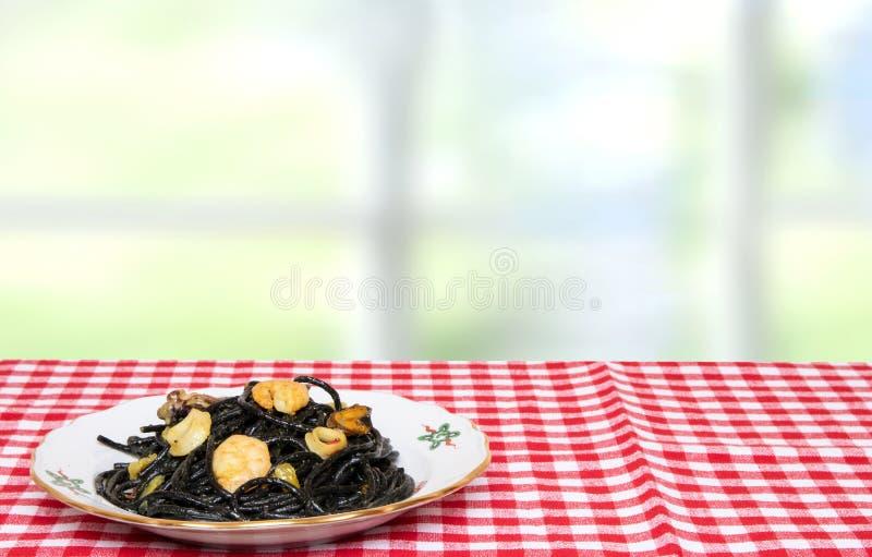 Sto?owy wierzcho?ek na owoce morza tle Zbli?enie ?r?dziemnomorscy czarni kluski z atramentem, mussels i garnelami na czerwieni cu obrazy royalty free