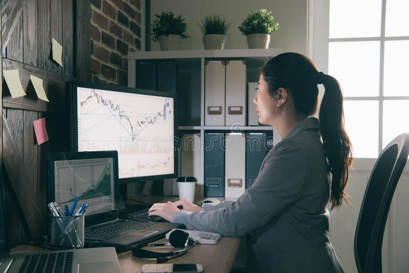 Stock analysts sitting in front of computer stock photo