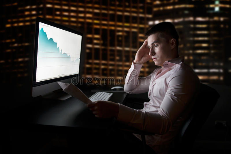 Stock analytic and broker looking at stock charts going down after sales report royalty free stock image