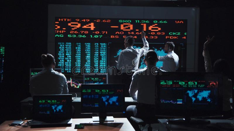 Stock broker team leaders in front of live feed. Two stock broker team leaders in front of a live, futuristic global market feed royalty free stock photography