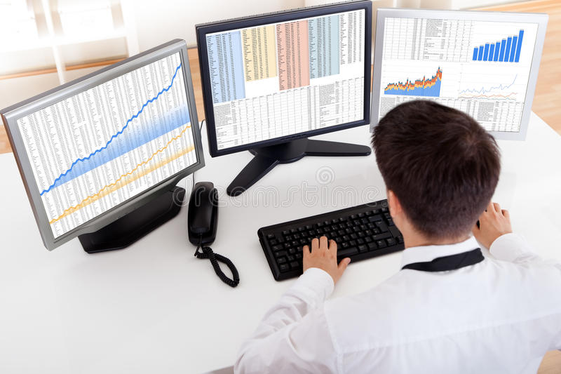Stock broker trading in a bull market. Over the shoulder view of the computer screens of a stock broker trading in a bull market showing ascending graphs royalty free stock images
