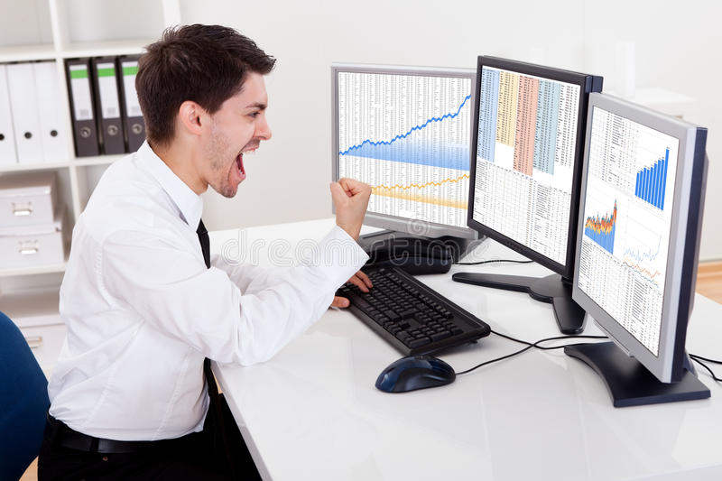 Stock broker trading in a bull market. Over the shoulder view of the computer screens of a stock broker trading in a bull market showing ascending graphs royalty free stock image