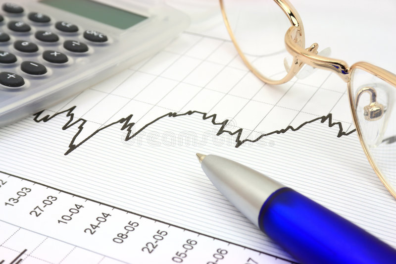 Stock chart. With calculator, blue pen and eyeglasses stock photography