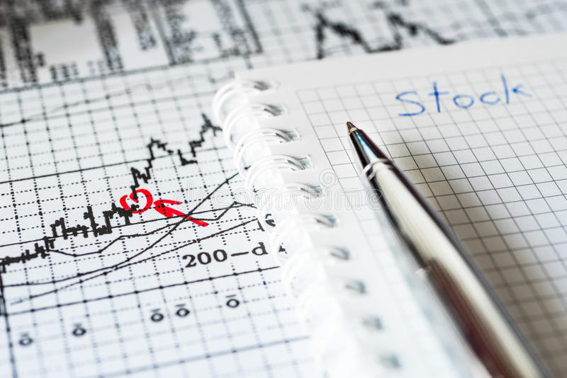 Stock Chart Analysis, writing the result. Stock Chart Analysis, calculation of income, mark the red in the graphic, a notebook with pen on the table stock images