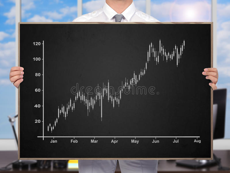 Stock chart. Businessman holding chalk board with drawing stock chart royalty free stock image