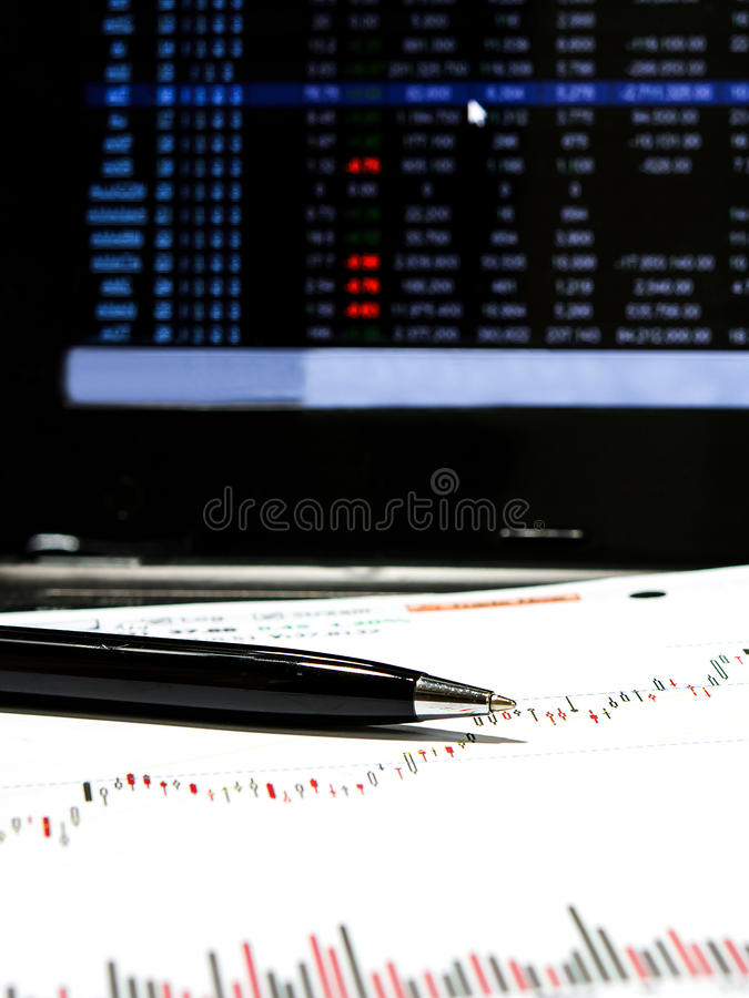 Stock chart data. With black pen and laptop monitor stock photos