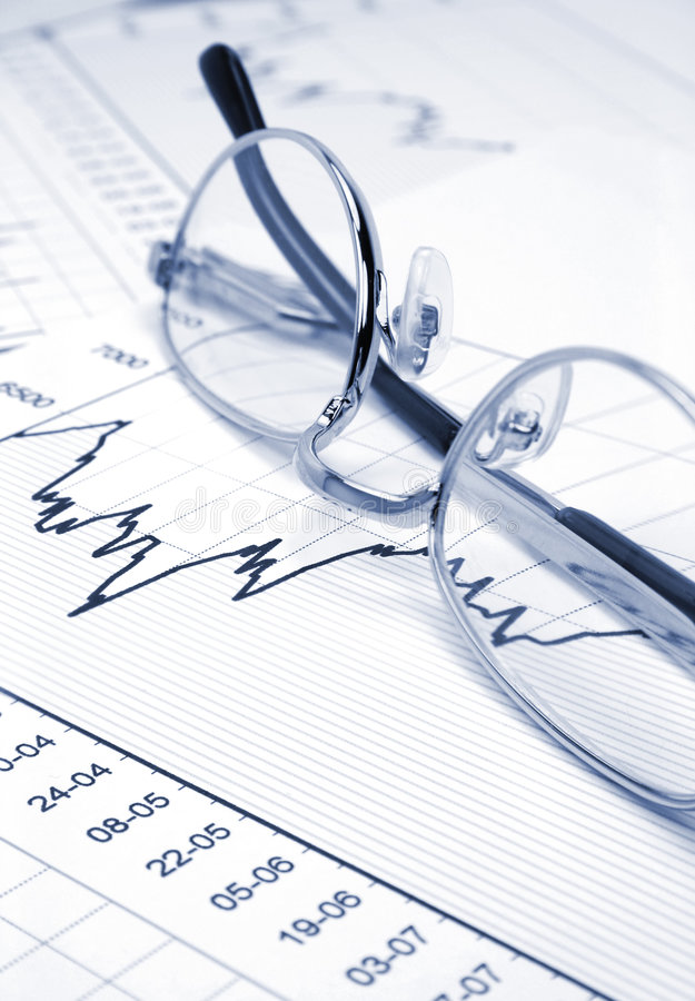 Stock chart and eyeglasses. (blue toned royalty free stock photography