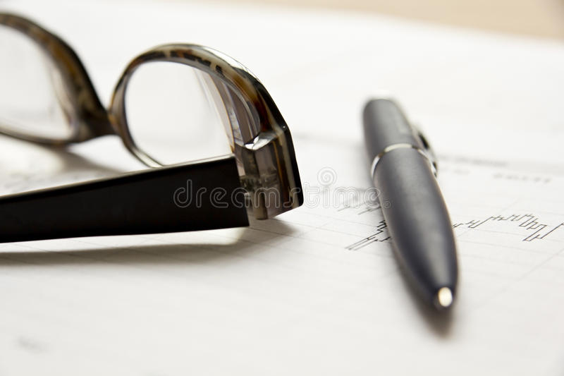 Stock chart with glasses and a pen royalty free stock images