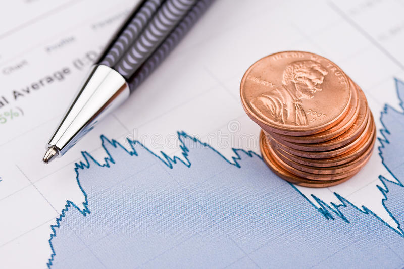 Stock chart and money. A stack of coins and pen sitting on stock chart royalty free stock image