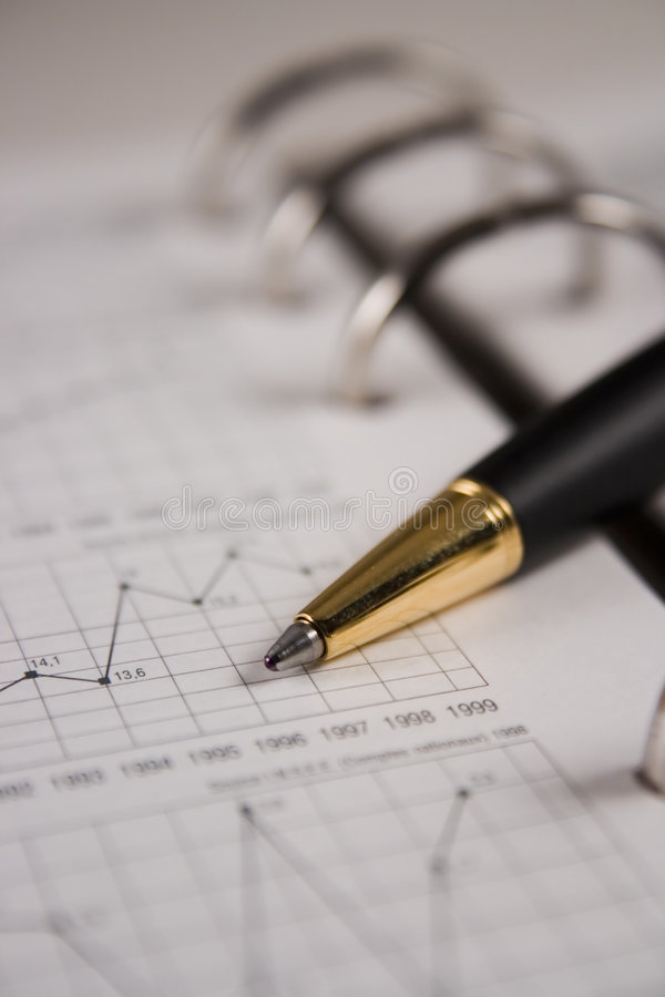 Stock chart with a pen. Pointing a graph stock photo
