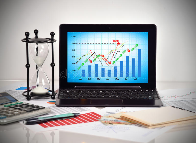Stock chart on screen notebook. Financial and business charts and report on table stock photos