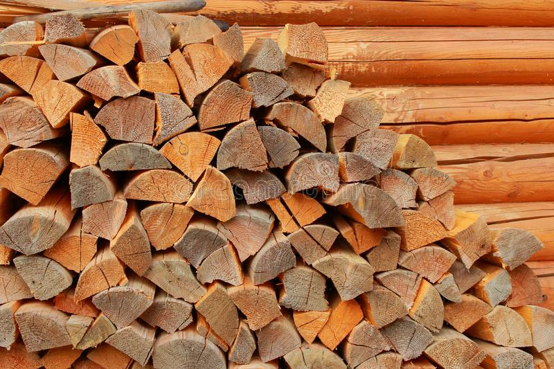 Stock of chipped firewood along wooden sauna wall as stocking for winter background. stock photo