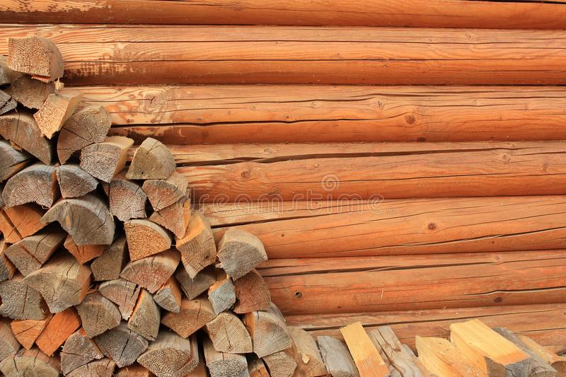 Stock of chipped firewood along wooden sauna wall with copy space. royalty free stock photo