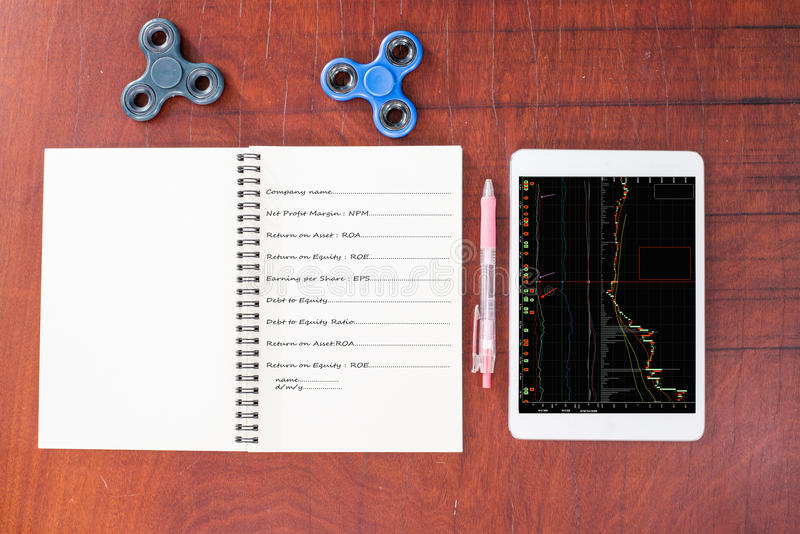 Stock graph on tablet, Pen, hand spinner, notebook on wood table royalty free stock image