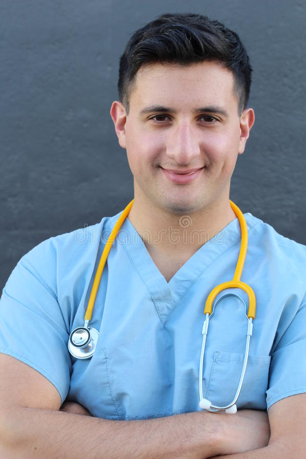 Stock image of medical intern standing with arms crossed over gray background.  royalty free stock photography