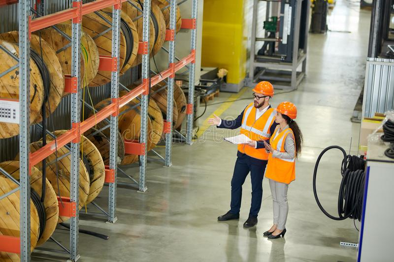 Stock Inventory at Factory. Full length portrait of bearded businessman wearing hardhat and holding clipboard doing inventory in production workshop, accompanied stock photos