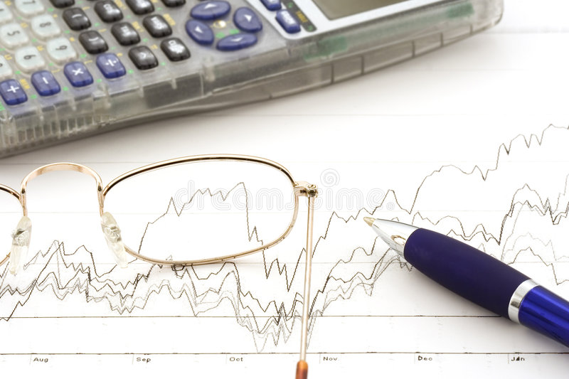 Stock market. Glasses,calculator,and pen on a stock chart stock images