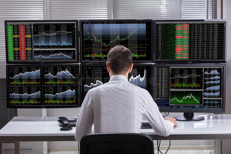 Stock Market Broker Analyzing Graphs On Computer Screens. Side View Of A Young Male Stock Market Broker Analyzing Graphs On Multiple Computer Screens stock photography