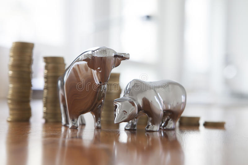 Stock market, bull and bear, figurines, stack of coins royalty free stock photo
